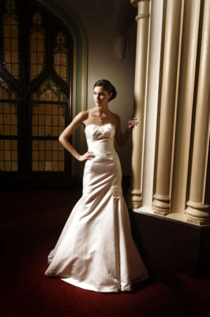 Image of a beautiful bride standing in a dimly lit room photo