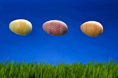 Image of 3 easter eggs in flight above green grass and against a blue sky photo
