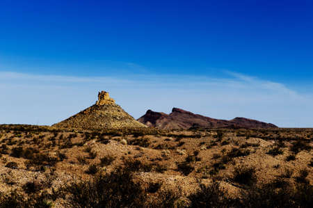 Image of a desert with shrubs, mountains in background and blue sky Stock Photo - 6185506
