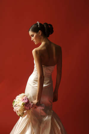 Image of a bride with body turned toward red wall looking down and to the side at bouquet photo