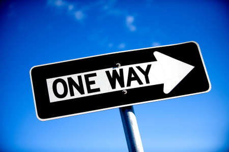 Image of a One Way Sign with blue sky