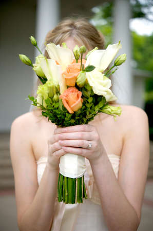Image of a bride holding her bouquet over her face Stock Photo