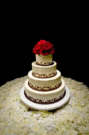 vanilla cake: Image of a traditional four tiered wedding cake with red roses on top sitting on a bed of white roses Stock Photo