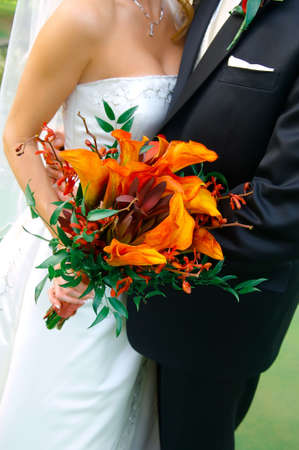 Image of a colorful bouquet being held by a bride and groom