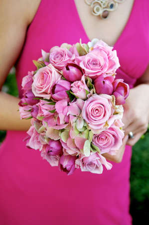 Image of a bridesmaid in a pink dress holding a pink bouquet photo