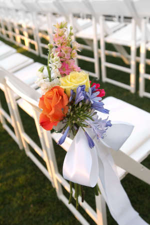 Image of a floral bouquet on a row of white chairs