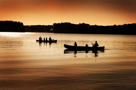 Image of silhouette of canoers on a lake photo