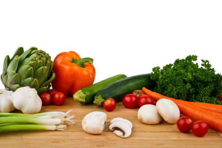 Image of a wood cutting board with assorted vegetables on a white background