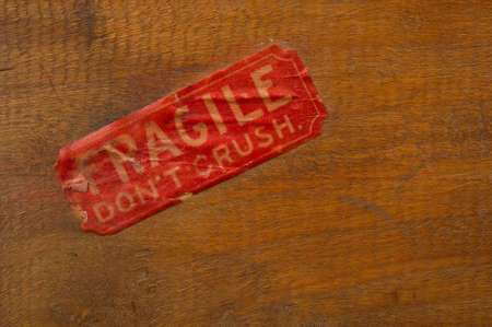 antiqued: Image of an antiqued fragile label on wood background Stock Photo