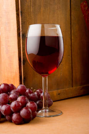 Image of a glass of wine and grapes next to wooden box Stock Photo