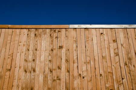 Afbeelding van een houten hek geschoten vanuit een lage hoek iets opzoeken met blauwe hemel