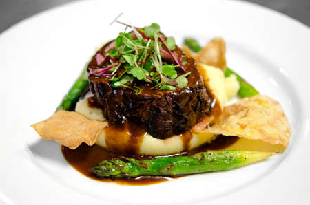 Image of a steak filet on a bed of mashed potatoes with asparagus, chips and gravy 스톡 콘텐츠