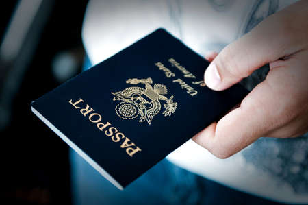 Image of a persons hand holding a passport