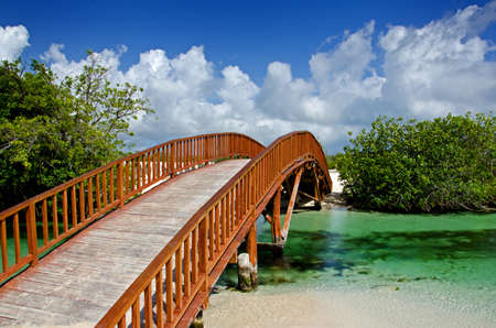 Image of an arched wooden bridge spanning over a small natural river flowing into the ocean Stock Photo