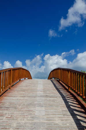 arched: Image of an arched wooden bridge that seems to lead into a beautiful sky