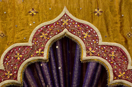 Closeup image detail of Indian fabric used in the decor of a wedding photo