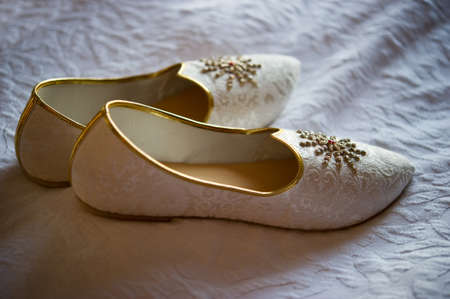 traditional culture: Image of mens Indian wedding shoes on a bed