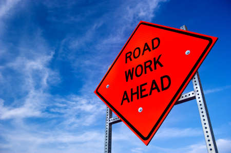road worker: Image of a bright orange road work ahead sign against a blue sky with light clouds
