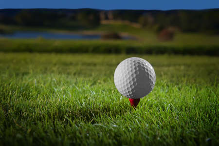 Image of a beautifully lit golf ball on a red tee with course in background Stock Photo - 10552164