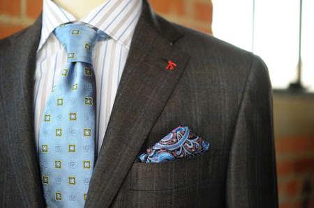 Afbeelding van een grijs pak met blauwe pinstriping en boutonniere