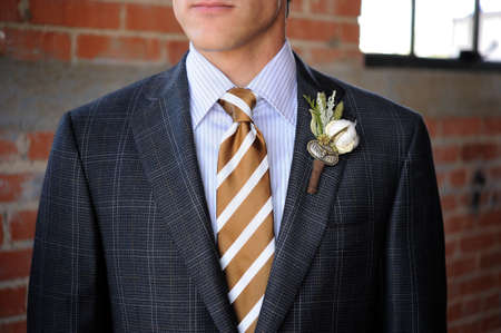 blue grey coat: Image of a Gray Plaid suit with tan stripes and boutonniere