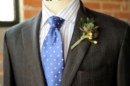 Image of a gray suit with blue tie and boutonniere photo