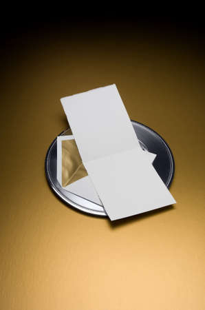 Image of a Blank Invitation with envelop on silver tray and gold background
