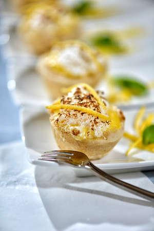 Image of lemon meringue tarts with garnish on white plates