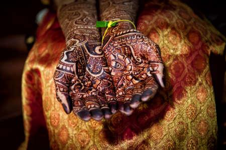 Afbeelding van prachtig gedetailleerde henna tatoeages ontworpen op de handen van een Indiase bruid draagt een traditionele sari Stockfoto