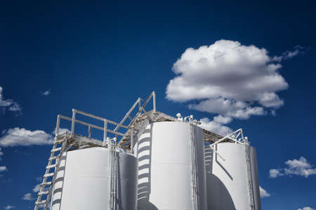 Image of industrial storage tanks against blue sky with clouds