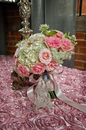 a brides wedding bouquet on a pink cloth photo