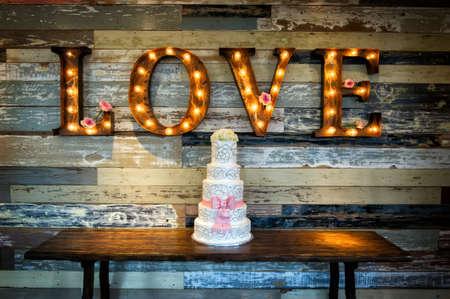 cérémonie mariage: un gâteau de mariage avec le mot amour comme sinage sur un fond rustique