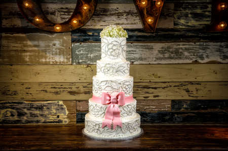 a beautiful wedding cake with a rustic background