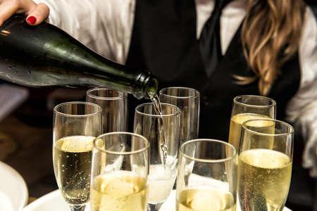 Afbeelding van een serveerster te vullen glazen champagne Stockfoto