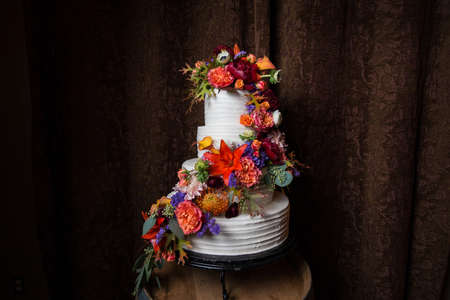 Beautiful white wedding cake with very colorful floral arrangement