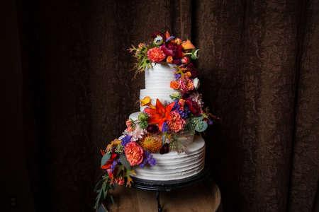 Schöne weiße Hochzeitstorte mit sehr bunten Blumenarrangement Standard-Bild - 51099923