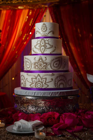 Artistically designed gold and purple Indian wedding cake