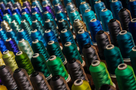 Multicolored threads on spindles in rows Stock Photo