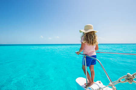 Girl looking at aqua blue sea on a boat