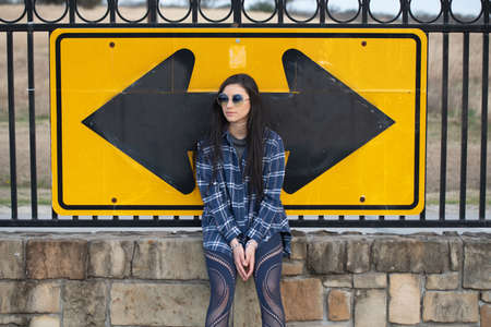 Image of a girl sitting on brick wall in front of a road sign