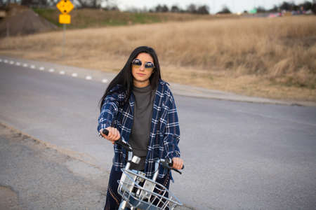 Image of a pretty brunette girl on a bike looking into the camera