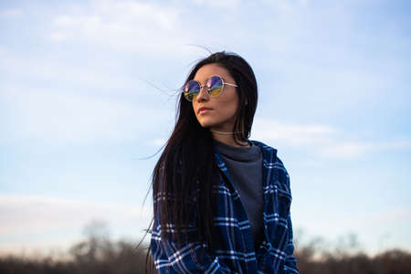 Image of a brunette girl looking over her shoulder wearing blue sunglasses Stock Photo
