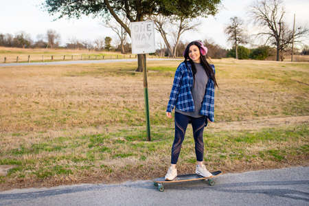 Image of brunette girl skateboarding wearing pink earmuffs and smiling at the camera Stock Photo