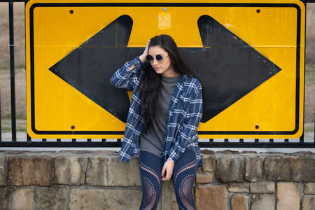 Candid image of a beautiful brunette girl sitting on a brick wall against a road sign
