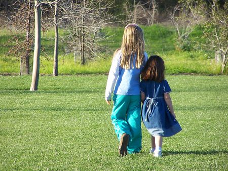 two girls walking on grass.