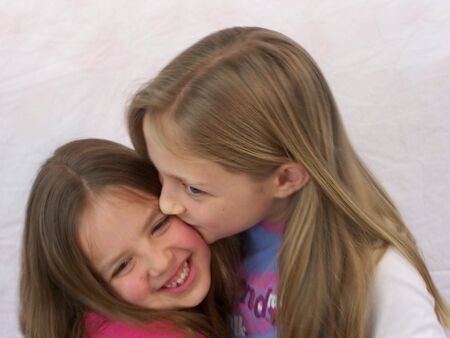 Two young sisters kissing