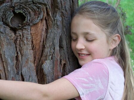 Girl hugging tree Stock Photo