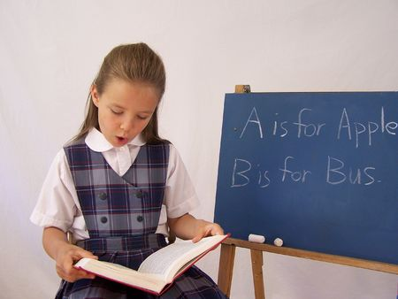 Girl with book at chalkboard Stock Photo