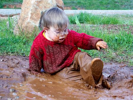 Boy playing in mud photo