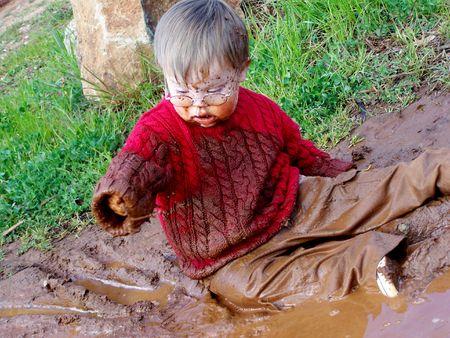 Boy playing in mud photo